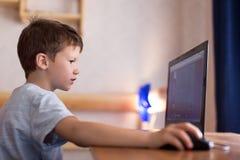 Маленький зависимый мальчик играя игру на компьтер-книжке стоковые фото