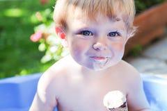 Маленький кавказский мальчик малыша есть мороженое в конусе Стоковая Фотография RF