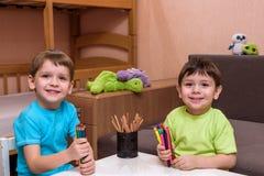 Маленький кавказский ребенок играя с сериями красочных пластичных блоков крытых Оягнитесь рубашка мальчика нося и иметь создавать Стоковая Фотография RF