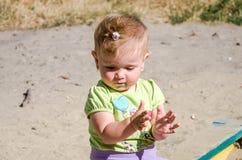 Маленький красивый младенец девушки играя в ящике с песком на спортивной площадке Стоковое фото RF