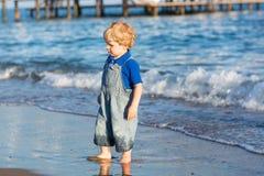 Маленький мальчик малыша имея потеху на пляже в лете Стоковое фото RF