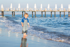 Маленький мальчик малыша имея потеху на пляже в лете Стоковая Фотография RF