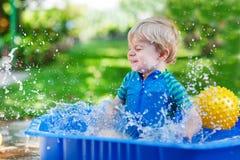 Маленький мальчик малыша имея потеху с брызгать воду в gar лета Стоковая Фотография