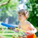 Маленький мальчик малыша имея потеху с брызгать воду в gar лета Стоковые Фотографии RF
