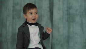 Маленький милый мальчик в усмехаться bowtie, делая смешные стороны, стильный вскользь ребенк акции видеоматериалы