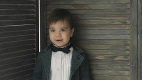 Маленький милый мальчик в усмехаться bowtie, делая смешные стороны, стильный вскользь ребенк видеоматериал