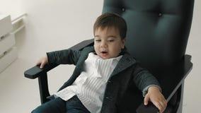 Маленький милый мальчик в усмехаться bowtie, делая смешные стороны, стильный вскользь ребенк сток-видео