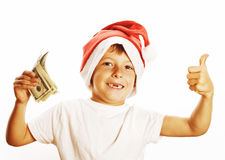 Маленький милый мальчик в шляпе santas красной изолированной с американцем наличных денег делает Стоковые Фотографии RF