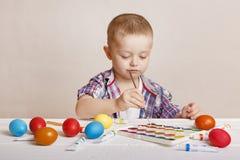 Маленький милый мальчик красит красочные пасхальные яйца стоковые фотографии rf
