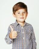 Маленький милый мальчик на белых tumbs вверх усмехаясь крупном плане жеста предпосылки, концепции людей образа жизни Стоковые Фото