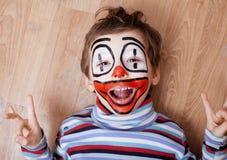 Маленький милый мальчик с facepaint любит клоун, поднимающее вверх pantomimic выражений близкое Стоковое Фото