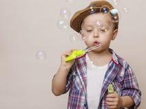 Маленький милый мальчик дует банки мыла стоковая фотография rf