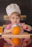 Маленький милый ребенк в крышке кашевара на кухне режет апельсины Mother& x27; хелпер s 2-ти летний Стоковые Фотографии RF