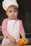 Маленький милый ребенк в крышке кашевара на кухне режет апельсины Mother& x27; хелпер s 2-ти летний Стоковые Изображения RF