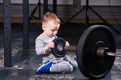 Маленький милый ребенок в sportwear в спортзале креста подходящем с штангой Стоковые Изображения
