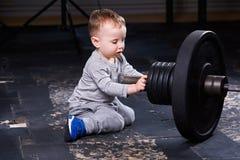 Маленький милый ребенок в sportwear в спортзале креста подходящем с штангой Стоковые Фото