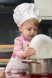 Маленький милый ребенок держа плиту в кухне 2-ти летний Стоковое Изображение