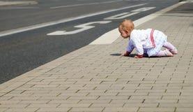Маленький младенец в белых одеждах вползая вдоль дороги стоковые изображения rf