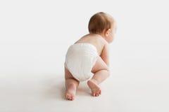 Маленький младенец в пеленке вползая на белом поле Стоковые Фотографии RF