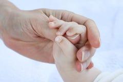 Маленький младенец держа руку матери Стоковая Фотография RF