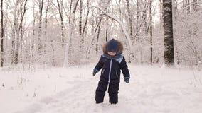 Маленький младенец играя с снегом в лесе зимы сток-видео