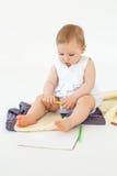 Маленький младенец сидя на поле на шотландке держа отметки Стоковая Фотография RF