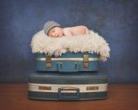 Маленький младенец спать на чемодане Стоковое фото RF