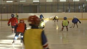 Маленький подогрев хоккеистов на льде (задний взгляд) сток-видео