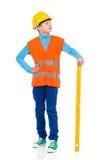 Маленький рабочий-строитель представляя с уровнем духа Стоковое Фото