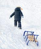 Маленький ребенок вытягивая голубой скелетон на снеге стоковые изображения