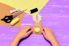 Маленький ребенок держит украшение оленей рождества войлока в руках Желтые и коричневые части войлока, поток, игла, ножницы Стоковое Изображение RF