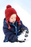 Маленький ребенок играя в снеге зимы делая снежный ком Стоковое Изображение RF