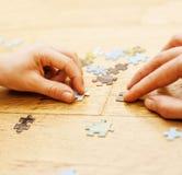 Маленький ребенок играя с головоломками на деревянном поле вместе с родителем, концепцией людей образа жизни, любящими руками к к Стоковые Фотографии RF