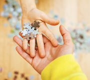 Маленький ребенок играя с головоломками на деревянном поле вместе с родителем, концепцией людей образа жизни, любящими руками к к Стоковая Фотография RF