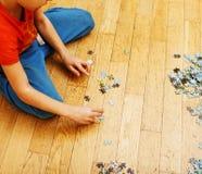 Маленький ребенок играя с головоломками на деревянном поле вместе с родителем, концепцией людей образа жизни, любящими руками к к Стоковое Изображение RF