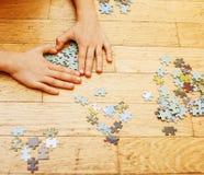 Маленький ребенок играя с головоломками на деревянном поле вместе с PA Стоковые Изображения RF