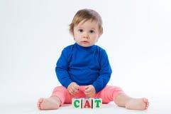 Маленький ребенок играя с dices изолированный на белой предпосылке Стоковое Фото