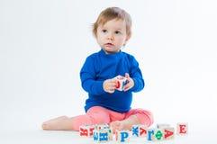 Маленький ребенок играя с dices изолированный на белой предпосылке Стоковая Фотография