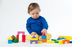 Маленький ребенок играя с dices изолированный на белой предпосылке Стоковые Изображения RF