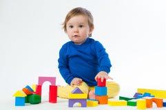 Маленький ребенок играя с dices изолированный на белой предпосылке Стоковое фото RF