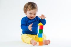 Маленький ребенок играя с dices изолированный на белой предпосылке Стоковое Изображение