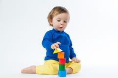 Маленький ребенок играя с dices изолированный на белой предпосылке Стоковые Изображения
