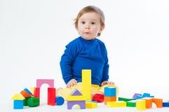 Маленький ребенок играя с dices изолированный на белой предпосылке Стоковые Фото