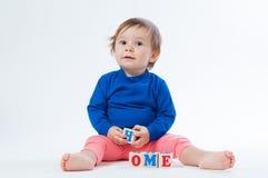 Маленький ребенок играя с dices на белой предпосылке Стоковые Фотографии RF