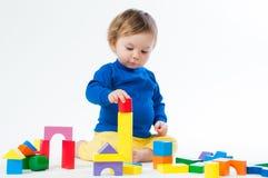 Маленький ребенок играя с dices на белой предпосылке Стоковое Изображение