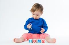 Маленький ребенок играя с dices на белой предпосылке Стоковая Фотография