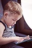Маленький ребенок используя сенсорную панель пока путешествующ мимо стоковые изображения