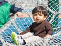 Маленький ребенок используя энергию на спортивной площадке Стоковые Фотографии RF
