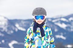 Маленький ребенок, катаясь на лыжах на наклоне снега в лыжный курорт в Австрии Стоковое Фото