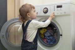 Маленький ребенок начинает стиральную машину Хелпер матери 2-ти летний стоковые изображения rf